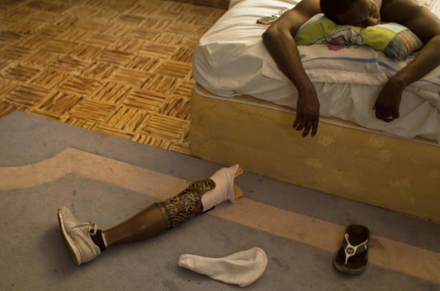 In this Jan. 17, 2013 photo, professional dancer Georges Exantus sleeps as his prosthetic limb lays on the floor in his bedroom in Port-au-Prince, Haiti. Exantus thought he'd never dance again. He was lucky just to be alive. The earthquake three years ago in Haiti's capital flattened the apartment where he was living, where he spent three days trapped under a heap of jagged rubble. After friends dug him out, doctors amputated his right leg just below the knee. Exantus says he has learned to ignore the long stares and quiet whispers, products of a longstanding stigma in Haiti for people with disabilities. Before the quake, few resources existed to accommodate Haiti's disabled, and many regard people with disabilities as misfits. (AP Photo/Dieu Nalio Chery)