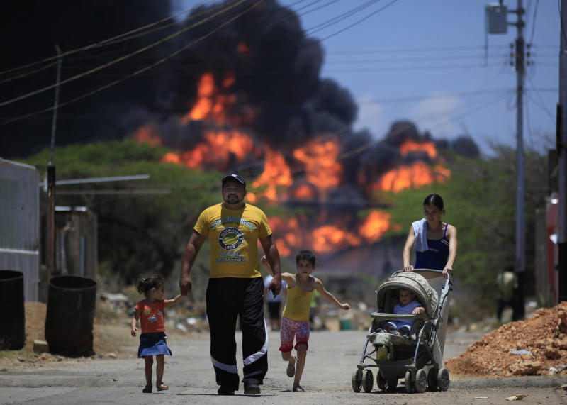 Members of a family walk on a street as flames rise after an explosion at the Amuay refinery near Punto Fijo, Venezuela, Sunday, Aug. 26, 2012. Venezuelans who live next to the country's biggest oil refinery said they smelled a strong odor of sulfur hours before a gas leak ignited in an explosion on Saturday that killed at least 39 people and injured more than 80. (AP Photo/Ariana Cubillos)
