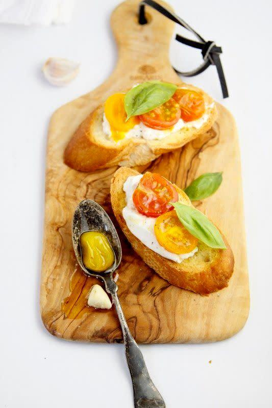 """<strong>Get the <a href=""""http://www.bellalimento.com/2013/09/09/roasted-heirloom-tomatoes-and-burrata-crostini/"""" rel=""""nofollow noopener"""" target=""""_blank"""" data-ylk=""""slk:Roasted Heirloom Tomatoes and Burrata Crostini recipe"""" class=""""link rapid-noclick-resp"""">Roasted Heirloom Tomatoes and Burrata Crostini recipe</a> from Bell'alimento</strong>"""