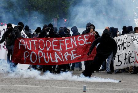 "Tear gas floats in the air as demonstrators walk behind a banner which reads, ""Populist Self-Defence"" during clashes at the traditional May Day labour union march in Paris"