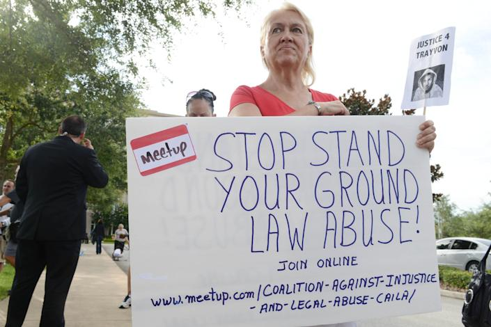 """Cathy Makowski demonstrates against what she calls the abuse of Florida's """"stand your ground"""" law in front of the Seminole County Courthouse in Sanford, Fla., after the shooting death of teenager Trayvon Martin in 2012."""