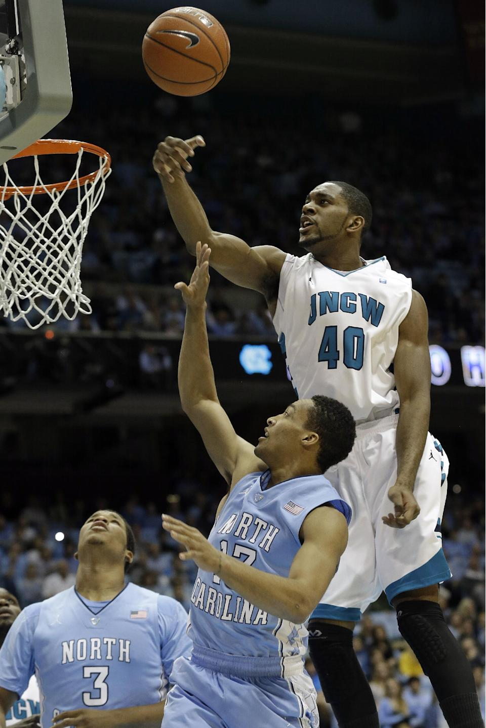 North Carolina's J.P. Tokoto (13) drives to the basket as UNC Wilmington's Cedrick Williams (40) blocks during the first half of an NCAA college basketball game in Chapel Hill, N.C., Tuesday, Dec. 31, 2013. North Carolina's Kennedy Meeks (3) stands under the basket. (AP Photo/Gerry Broome)