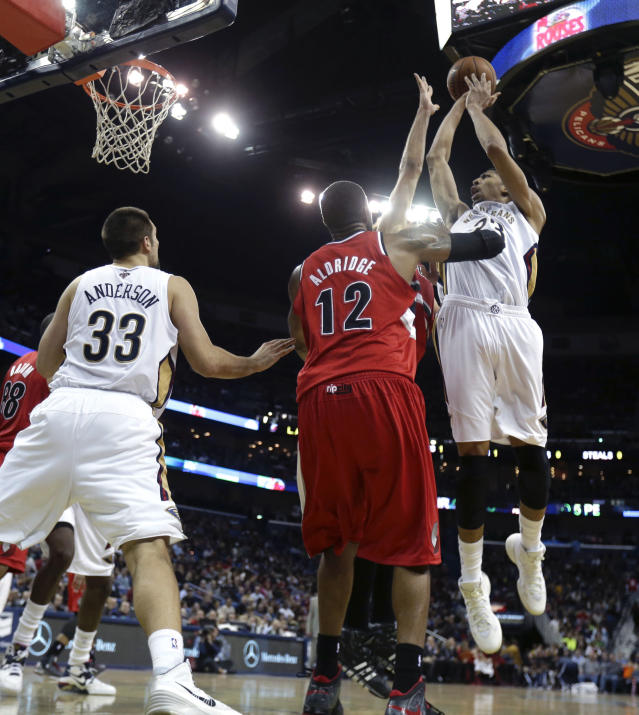 New Orleans Pelicans forward Anthony Davis (23) shoots over Portland Trail Blazers forward LaMarcus Aldridge (12) as Pelicans forward Ryan Anderson (33) positions under the basket in the first half of an NBA basketball game in New Orleans, Monday, Dec. 30, 2013. (AP Photo/Gerald Herbert)