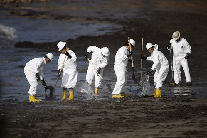 Workers clean an oil spill on a California beach. There's plenty more work where that came from. (Photo: Lucy Nicholson / Reuters)
