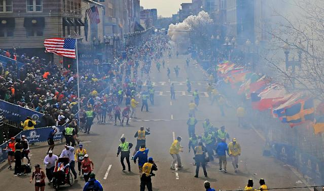 People react as an explosion goes off near the finish line of the 2013 Boston Marathon in Boston, Monday, April 15, 2013. Two explosions went off at the Boston Marathon finish line on Monday, sending authorities out on the course to carry off the injured while the stragglers were rerouted away from the smoking site of the blasts. (AP Photo/The Boston Globe, David L Ryan) MANDATORY CREDIT