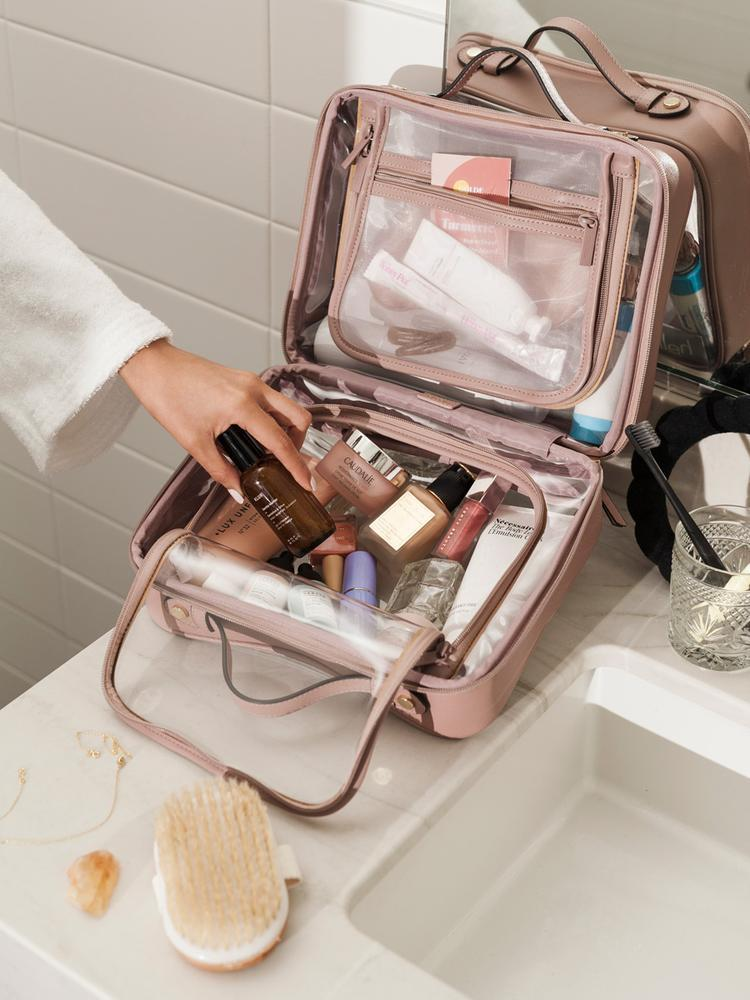 """<h2>CALPAK Clear Cosmetics Case</h2><br><strong>The Type</strong>: Toiletry Travel Bag<br><br><strong>The Hype</strong>: 4.8 out of 5 stars and 72 reviews<br><br><strong>What Travelers Say</strong>: """"I bought the smaller version of this for everyday and weekend travel. I just received the larger size and will be using it for flying. I can fit all of my toiletries, makeup. and hair supplies. You have to buy both, and you will never need another makeup bag. They are very well constructed and easy to clean."""" — <em>Mary Ann A., CALPAK Reviewer<br></em><br><em>Shop</em> <a href=""""http://calpaktravel.com"""" rel=""""nofollow noopener"""" target=""""_blank"""" data-ylk=""""slk:CALPAK"""" class=""""link rapid-noclick-resp""""><strong><em>CALPAK</em></strong></a><br><br><strong>CALPAK Travel</strong> Clear Cosmetics Case, $, available at <a href=""""https://go.skimresources.com/?id=30283X879131&url=https%3A%2F%2Fwww.calpaktravel.com%2Fproducts%2Fclear-cosmetic-case%2Fmauve"""" rel=""""nofollow noopener"""" target=""""_blank"""" data-ylk=""""slk:CALPAK Travel"""" class=""""link rapid-noclick-resp"""">CALPAK Travel</a>"""
