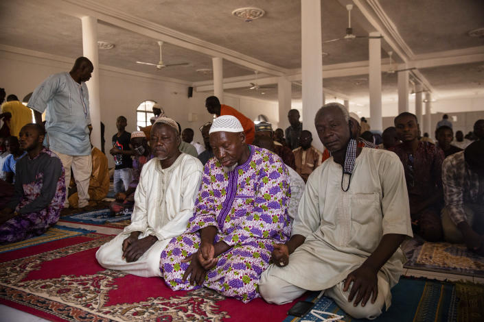 Muslim worshippers participate in Friday prayers at the Sangoulé Lamizana military camp in Ouagadougou, Burkina Faso, Friday April 9, 2021. Just seven chaplains, hailing from Protestant, Catholic and Muslim faiths, are charged with spiritually advising some 11,000 soldiers and helping maintain their morale. (AP Photo/Sophie Garcia)