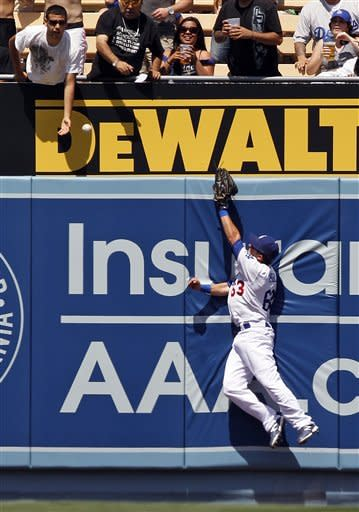 Los Angeles Dodgers center fielder Matt Angle can't get to a two-run homer by Los Angeles Angels' Ryan Langerhans during the fourth inning of an exhibition baseball game at Dodger Stadium in Los Angeles on Wednesday, April 4, 2012. (AP Photo/Reed Saxon)