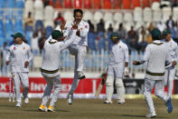 Pakistan pacer Mohammad Abbas, center, celebrates with teammates after taking the wicket of Bangladesh batsman Najmul Hossain Shanto during the first day of their 1st test cricket match at Rawalpindi cricket stadium in Rawalpindi, Pakistan, Friday, Feb. 7, 2020. (AP Photo/Anjum Naveed)