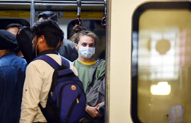A woman is pictured at the Rajiv Chowk metro station in New Delhi wearing a mask on 13 March. India has had 81 confirmed cases. (Getty Images)