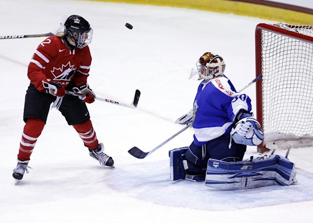 Finland goalie Noora Raty (30) makes a save on Canada's Meghan Agosta-Marciano (2) during the third period of a Four Nations Cup women's hockey game on Tuesday, Nov. 5, 2013, in Lake Placid, N.Y. Canada won, 3-1. (AP Photo/Mike Groll)
