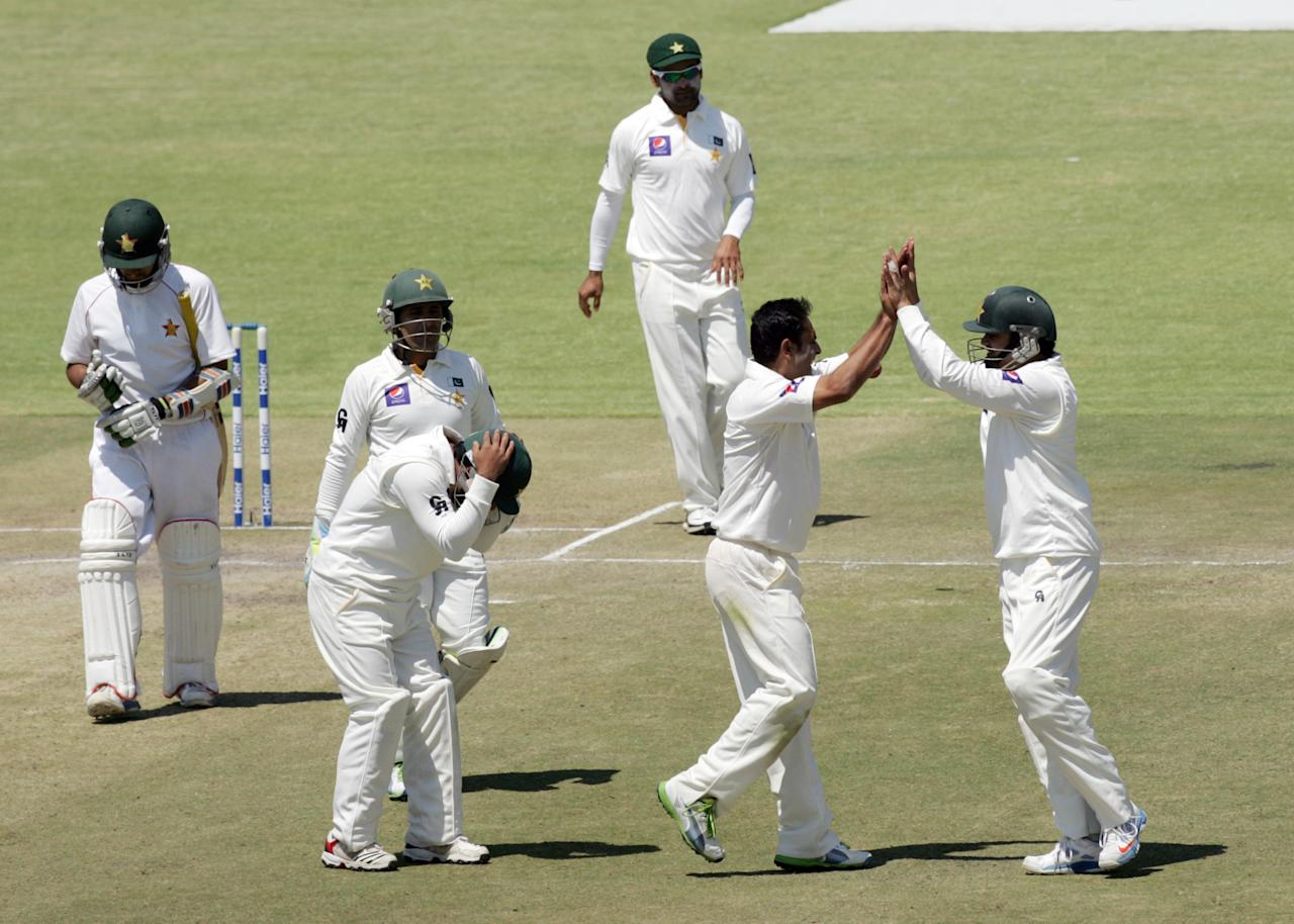 Pakistan's players celebrate the wicket of Sikanda Raza Butt during the fifth day of the first test match between Pakistan and hosts Zimbabwe at the Harare Sports Club September 7, 2013.  AFP PHOTO / JEKESAI NJIKIZANA        (Photo credit should read JEKESAI NJIKIZANA/AFP/Getty Images)