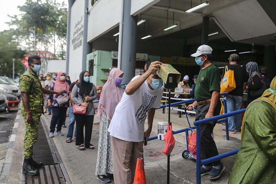 People have their temperature checked before entering the Seksyen 6 wet market in Shah Alam May 11, 2021. — Picture by Yusof Mat Isa