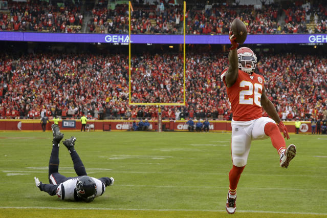 Kansas City Chiefs running back Damien Williams (26) scores a touchdown ahead of Houston Texans linebacker Jacob Martin (54) during the first half of an NFL divisional playoff football game, in Kansas City, Mo., Sunday, Jan. 12, 2020. (AP Photo/Charlie Riedel)