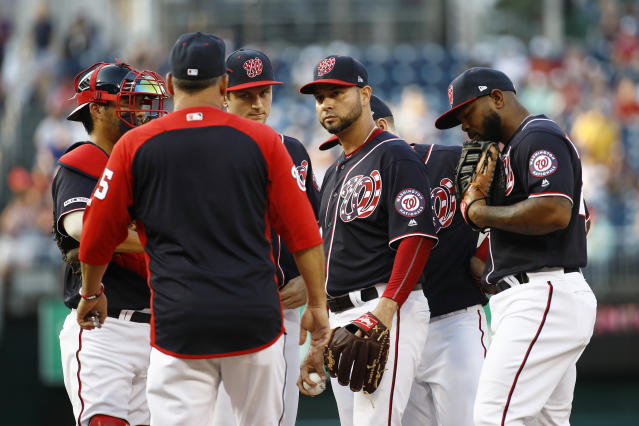 Washington Nationals starting pitcher Anibal Sanchez, center, gathers on the mound with teammates and pitching coach Paul Menhart, second from left, after walking Los Angeles Dodgers' Max Muncy to load the bases in the first inning of a baseball game, Friday, July 26, 2019, in Washington. (AP Photo/Patrick Semansky)