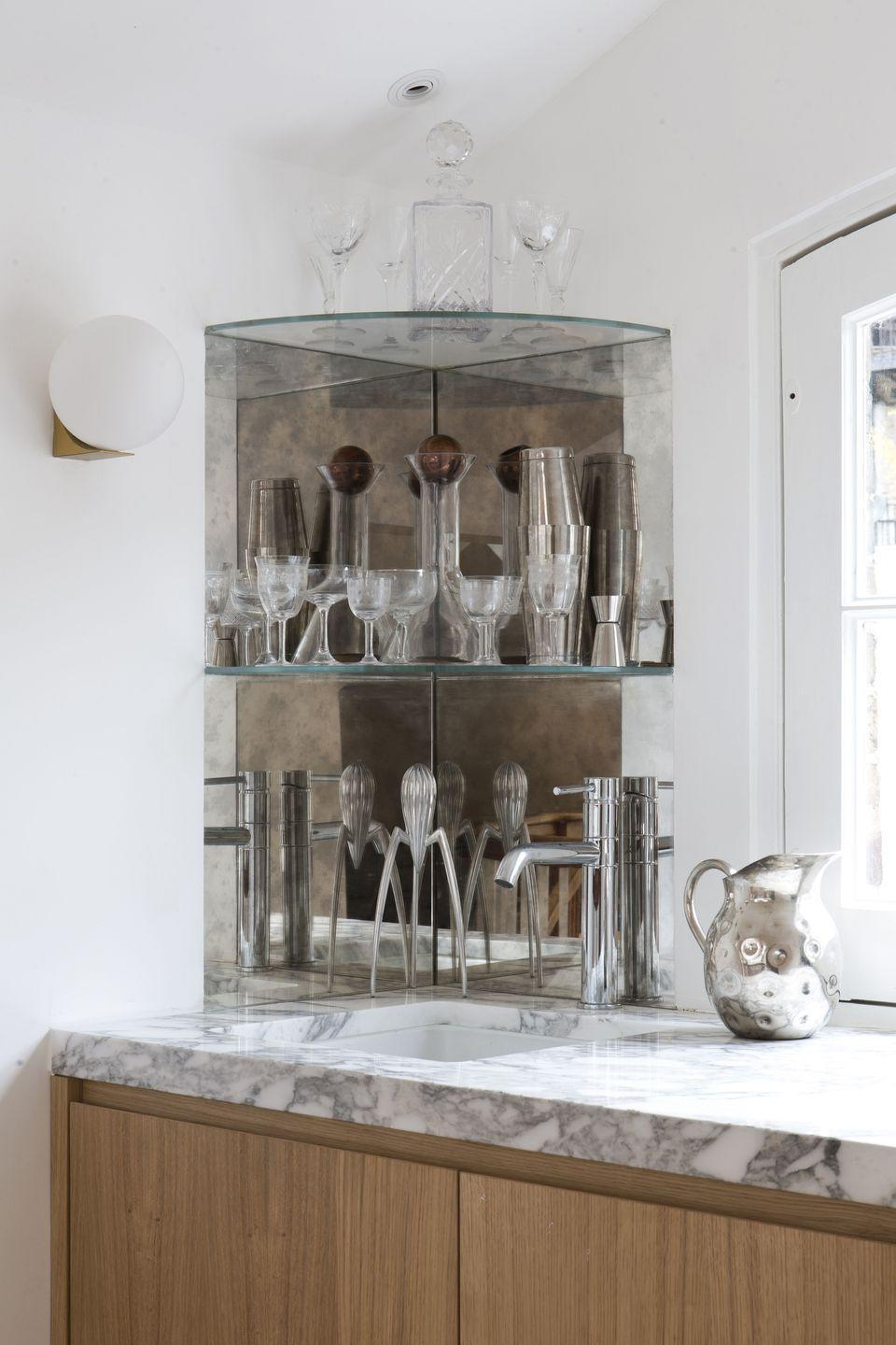 """<p>""""This shows the bar area in a small window space in the top of the house. It's where the hay used to be brought into the loft. We needed to maximise the bar area, so built two corner shelves to house our vintage glasses, cocktail shakers and decanters. The surface is Italian marble to give texture.""""</p>"""