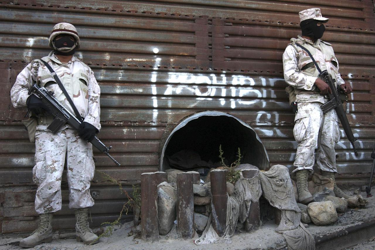 File-This June 4, 2010 file photo shows Mexican army soldiers standing guard next to a tunnel at the border wall in Tijuana, Mexico. More than 75 such underground passages have been found along the border since 2008, concentrated largely in California and Arizona. The job of searching these networks can be dangerous, so the U.S. Border Patrol is unveiling its latest technology in the underground war, a wireless, camera-equipped robot that can do the job in a fraction of the time. (AP Photo,File)
