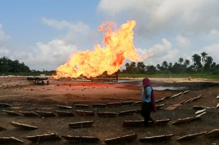 A woman walks amid rows of wooden trays laid with tapioca close to a burning gas flaring furnace at a flow station in Ughelli, Delta State