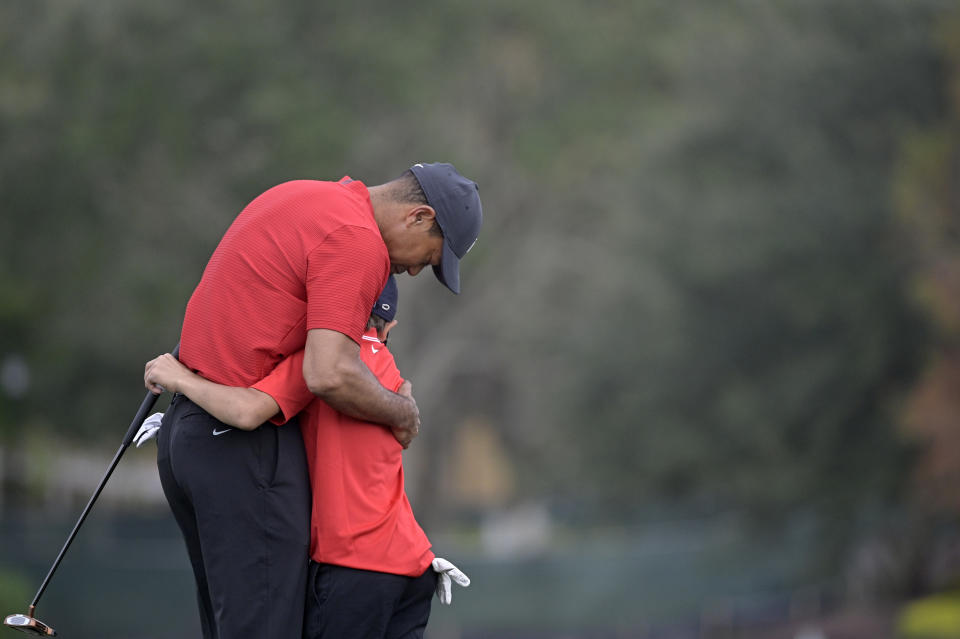 Tiger Woods hugs his son Charlie after finishing on the 18th green during the final round of the PNC Championship golf tournament, Sunday, Dec. 20, 2020, in Orlando, Fla. (AP Photo/Phelan M. Ebenhack)