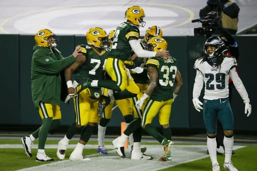 Green Bay Packers' Aaron Jones is congratulated by quarterback Aaron Rodgers (12) after running for a 77-yard touchdown during the second half of an NFL football game against the Philadelphia Eagles Sunday, Dec. 6, 2020, in Green Bay, Wis. (AP Photo/Mike Roemer)