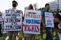 Demonstrators hold signs during a march for voting rights, marking the 58th anniversary of the March on Washington, Saturday, Aug. 28, 2021, in Washington. Hundreds of thousands of voting rights advocates rallied across the country Saturday to call for sweeping protections against a further erosion of the Voting Rights Act of 1965. (AP Photo/Jose Luis Magana)