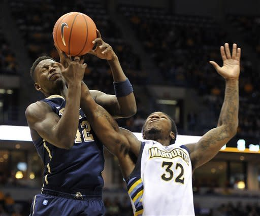Pittsburgh's Talib Zanna (42) and Marquette's Jae Crowder (32) fight for the rebound during the first half of an NCAA college basketball game Saturday, Jan. 14, 2012, in Milwaukee. (AP Photo/Jim Prisching)