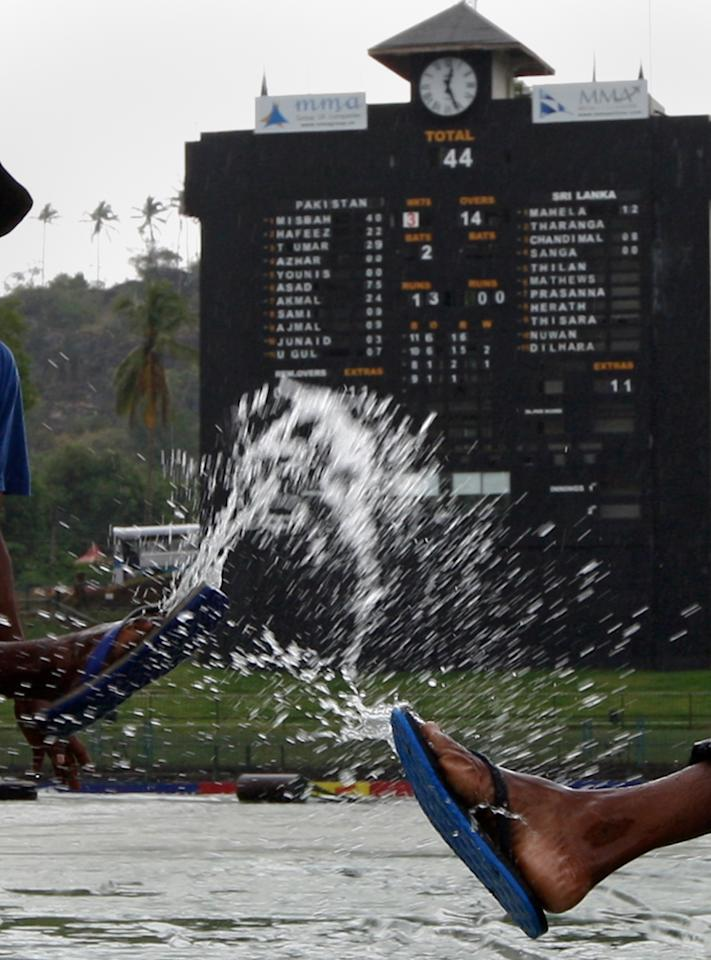 KANDY, SRI LANKA - JULY 09:  Ground staff splash water as rain delays the second day of third test between Sri Lanka and Pakistan at Pallekele International Cricket Stadium on July 9, 2012 in Kandy, Sri Lanka.  (Photo by Buddhika Weerasinghe/Getty Images)