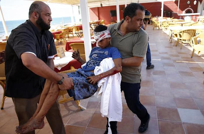 Palestinian employees of Gaza City's al-Deira hotel carry a wounded boy following an Israeli military strike on a beach, on July 16, 2014 (AFP Photo/Thomas Coex)