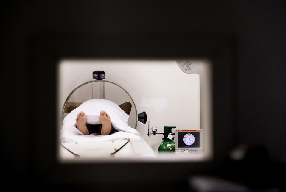 SANTO ANDRE, BRAZIL - MAY 17: A COVID-19 patient receives a CT scan at a field hospital set up in the Pedro Dell'Antonia Sports Complex on May 17, 2021 in Santo Andre, Brazil. Health experts are warning that Brazil should brace for a new surge of COVID-19 amid a slow vaccine rollout and relaxed restrictions. The state of Sao Paulo has registered over 3 million cases of COVID-19 and more than 100,000 deaths. Over 435,000 people have been killed in Brazil by COVID-19, second only to the U.S. (Photo by Mario Tama/Getty Images)