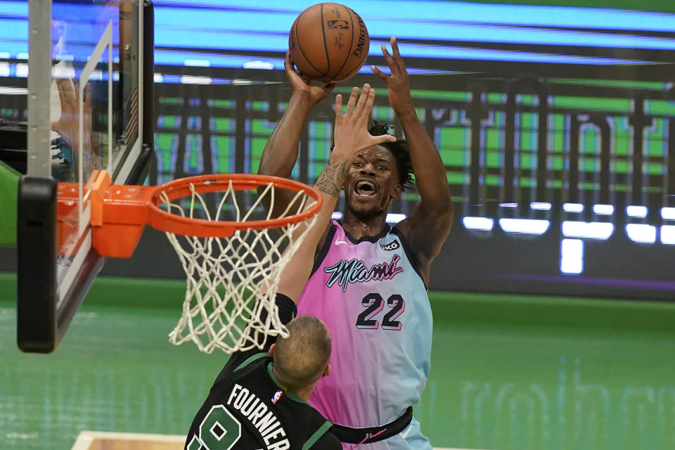 Miami Heat's Jimmy Butler (22) shoots at the basket as Boston Celtics' Evan Fournier (94) tries to block in the second half of a basketball game, Sunday, May 9, 2021, in Boston. (AP Photo/Steven Senne)