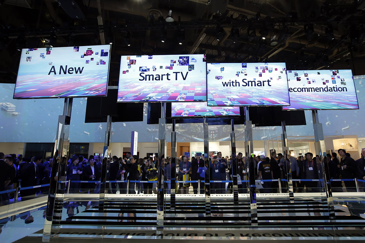 Show attendees look at an installation made with smart TVs at the Samsung booth at the International Consumer Electronics Show.