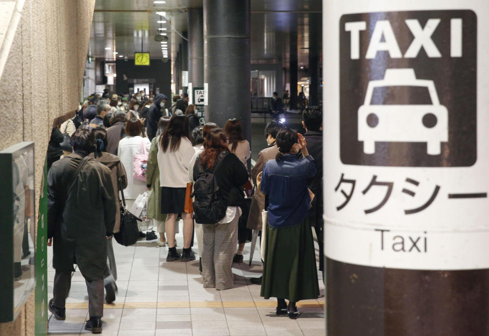 People queue up for taxi as train services are suspended following an earthquake in Sendai, Miyagi prefecture, Japan Saturday, March 20, 2021. A strong earthquake struck Saturday off northern Japan, shaking buildings even in Tokyo and triggering a tsunami advisory for a part of the northern coast. (Kyodo News via AP)