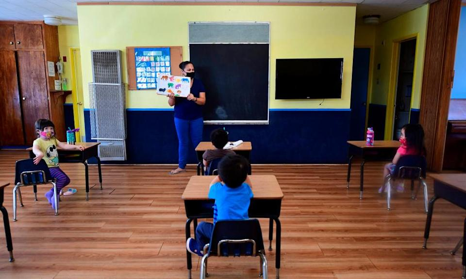 Instructor Chablis Torres reads to children in a pre-school class, wearing masks and at desks spaced apart as per coronavirus guidelines during summer school sessions at Happy Day school in Monterey Park, California, in July.
