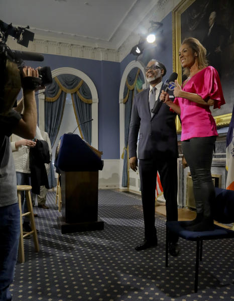 Reporter Kimberly Richardson stands on a chair to interview New York City Councilman Robert Cornegy, Jr., after he was awarded the Guinness World Record's for tallest male politician, Wednesday March 27, 2019, at City Hall in New York. (AP Photo/Bebeto Matthews)