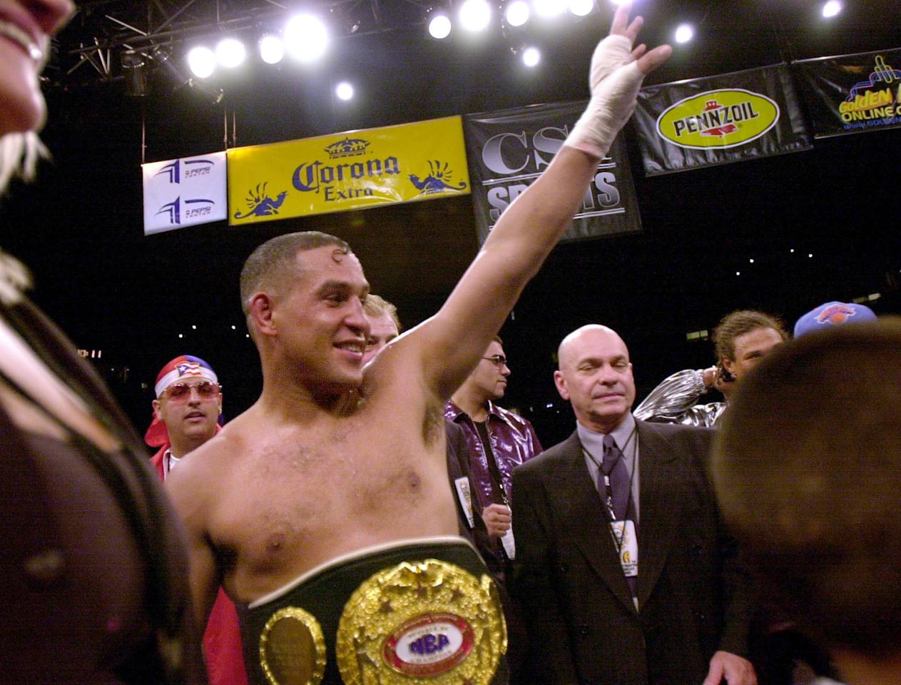 """(FILES)Hector Camacho from Puerto Rico waves to the crowd, wearing the NBA Super Middle Weight Championship belt, after winning over Roberto Duran from Panama by decision in 12 rounds at the Pepsi Center in this July 14, 2001 photo in Denver, Colorado.  Former three time world boxing champion Hector """"Macho"""" Camacho was seriously injured the evening of November 20, 2012 after being shot in the neck in Puerto Rico, local media reported. Camacho, 50, was being driven in a car when he was hit in the head by gunshot from another vehicle around 7:00 pm local time, the Primera Hora de Puerto Rico newspaper reported on its website. Ernesto Torres, director of the Centro Medico de Rio Piedras, was cautious about Camacho's chances of survival, saying that a bullet had fractured two bones in his neck. """"It appears the bullet struck a bone and was deflected without going into the brain,"""" Torres told the newspaper. An earlier report said a single bullet struck the left side of Camacho's jaw.  AFP PHOTO MARK LEFFINGWELLMARK LEFFINGWELL/AFP/Getty Images"""