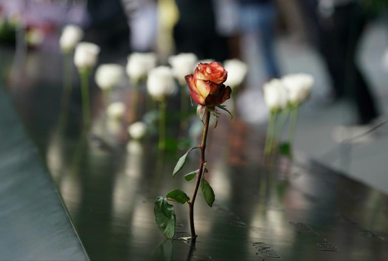 People leave flowers during the September 11 Commemoration Ceremony at the 9/11 Memorial at the World Trade Center on September 11, 2019, in New York