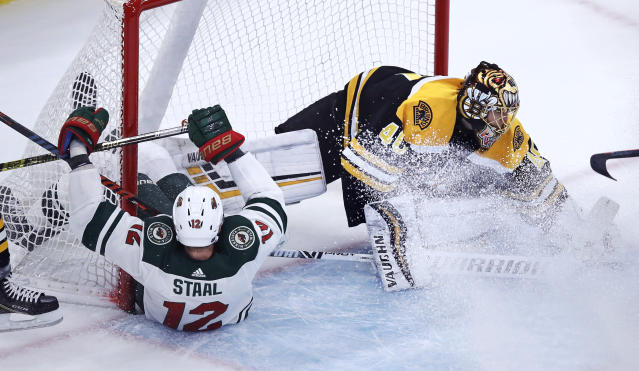 Boston Bruins goaltender Tuukka Rask, right, makes a save as Minnesota Wild center Eric Staal (12) slips into the net during the first period of an NHL hockey game in Boston, Tuesday, Jan. 8, 2019. (AP Photo/Charles Krupa)