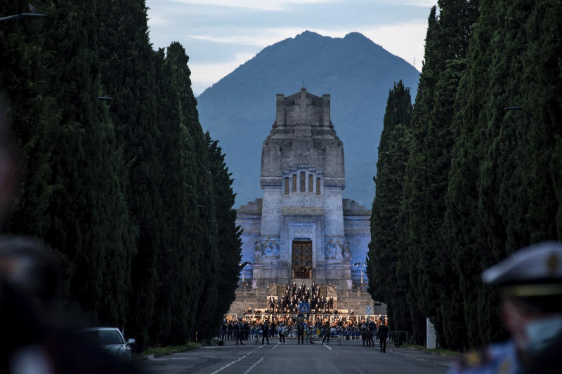 """Musicians perform in front of the Bergamo cemetery, Italy, Sunday, June 28, 2020. Italy bid farewell to its coronavirus dead on Sunday with a haunting Requiem concert performed at the entrance to the cemetery of Bergamo, the hardest-hit province in the onetime epicenter of the outbreak in Europe. President Sergio Mattarella was the guest of honor, and said his presence made clear that all of Italy was bowing down to honor Bergamo's dead, """"the thousands of men and women killed by a sickness that is still greatly unknown and continues to threaten the world."""" (Claudio Furlan/LaPresse via AP)"""