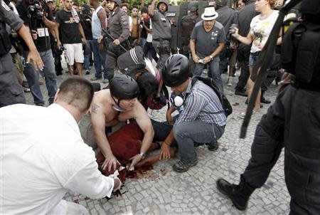 People help cameraman Andrade Santiago after he was injured during a protest in Rio de Janeiro