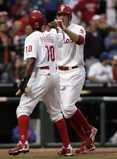 Philadelphia Phillies' Juan Pierre, left, taps fists with Hunter Pence after Pence's two-run homer in the first inning of a baseball game with the New York Mets, Tuesday, May 8, 2012, in Philadelphia. (AP Photo/Tom Mihalek)