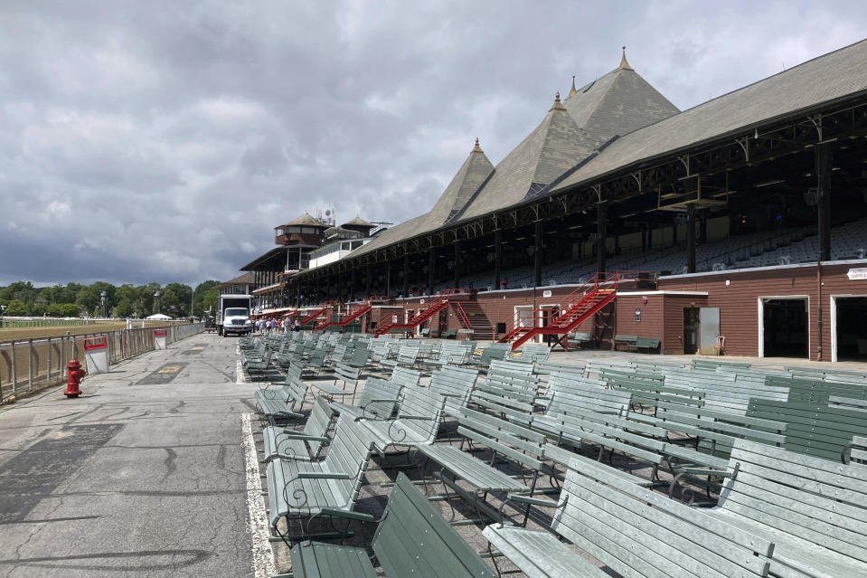 The grandstands at Saratoga race track sits empty, Wednesday, July 14, 2021, in Saratoga Springs, N.Y. A year after racing was conducted without fans due to the coronavirus pandemic, the New York Racing Association's summer meet at the oldest racetrack in the country begins Thursday. (AP Photo/John Kekis)