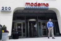 FILE - A man stands outside an entrance to a Moderna, Inc., building, Monday, May 18, 2020, in Cambridge, Mass. A second COVID-19 vaccine moved closer to joining the U.S. fight against the pandemic Thursday, Dec. 17, 2020 as government experts convened for a final public review of its safety and effectiveness. The shot from Moderna and the National Institutes of Health is urgently needed as the country continues to record ever-higher numbers of new cases, hospitalizations and deaths ahead of more holiday travel and family gatherings. FDA's OK is expected shortly after the all-day meeting concludes. (AP Photo/Bill Sikes, file)