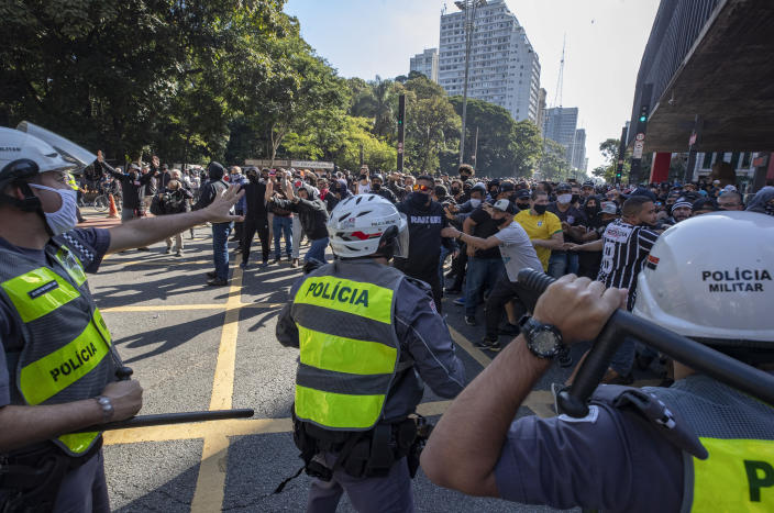 Police clash with demonstrators during a protest against fascism, President Jair Bolsonaro and to defend democracy in Sao Paulo, Brazil, Sunday, May 31, 2020. Police used tear gas to disperse anti-government protesters in Brazil's largest city as they began to clash with small groups of demonstrators loyal to President Jair Bolsonaro. (AP Photo/Andre Penner)