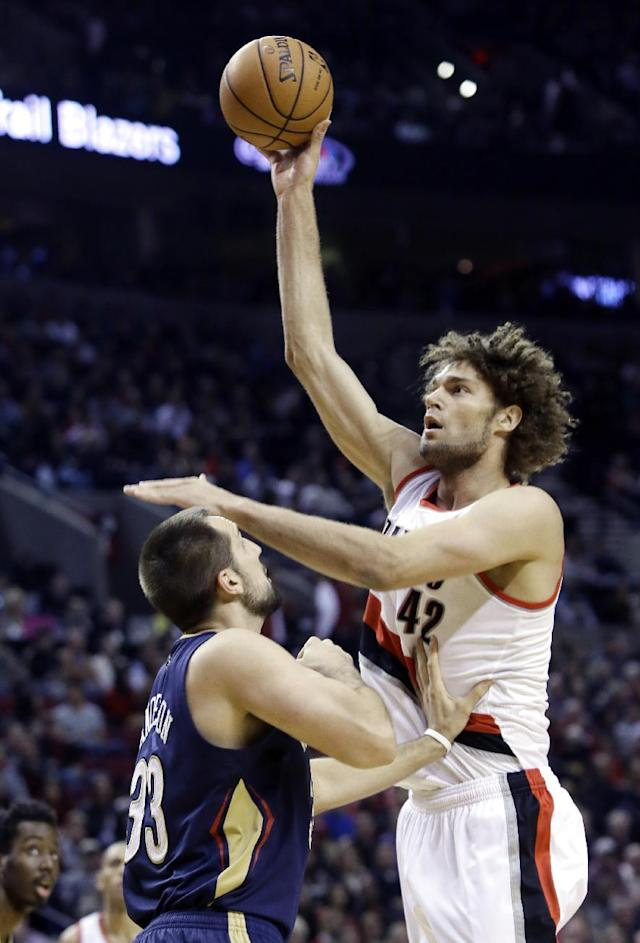 Portland Trail Blazers center Robin Lopez, right, shoots over New Orleans Pelicans forward Ryan Anderson during the first half of an NBA basketball game in Portland, Ore., Saturday, Dec. 21, 2013. (AP Photo/Don Ryan)