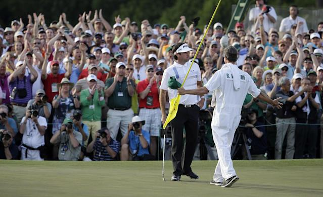 Bubba Watson is congratulated by his caddie Ted Scott after winning the Masters golf tournament Sunday, April 13, 2014, in Augusta, Ga. (AP Photo/Darron Cummings)