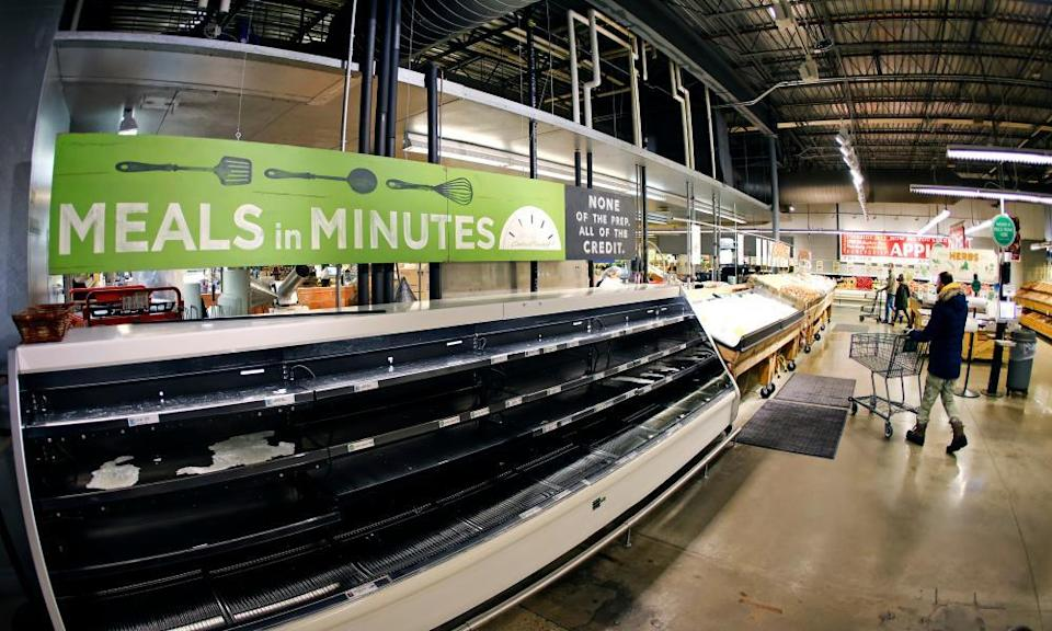 People shop depleted produce aisles at Central Market on Thursday in Fort Worth, Texas.