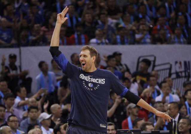 Dirk Nowitzki of Dallas Mavericks, center, reacts against Philadelphia 76ers during the Shenzhen basketball match of the NBA China Games in Shenzhen city, south China's Guangdong province, Monday, Oct. 8, 2018. (AP Photo/Kin Cheung)