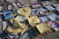 Piles of exercise books and shoe insoles dry in the sun near Yubei Agricultural and Aquatic Products World in Xinxiang in central China's Henan Province, Monday, July 26, 2021. Record rain in Xinxiang last week left the produce and seafood market soaked in water. Dozens of people died in the floods that immersed large swaths of central China's Henan province in water. (AP Photo/Dake Kang)