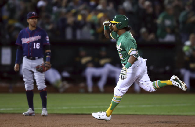 Oakland Athletics' Khris Davis, right, celebrates as he passes Minnesota Twins' Ehire Adrianza (16) after hitting a two-run home run off Jose Berrios during the first inning of a baseball game Friday, Sept. 21, 2018, in Oakland, Calif. (AP Photo/Ben Margot)