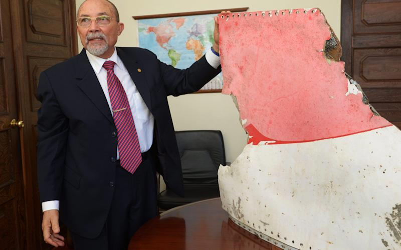 Joao de Abreu, president of Mozambique Civil Aviation Authority, shows one of three pieces of plane debris, possibly belonging to missing flight MH370 - Credit: PA